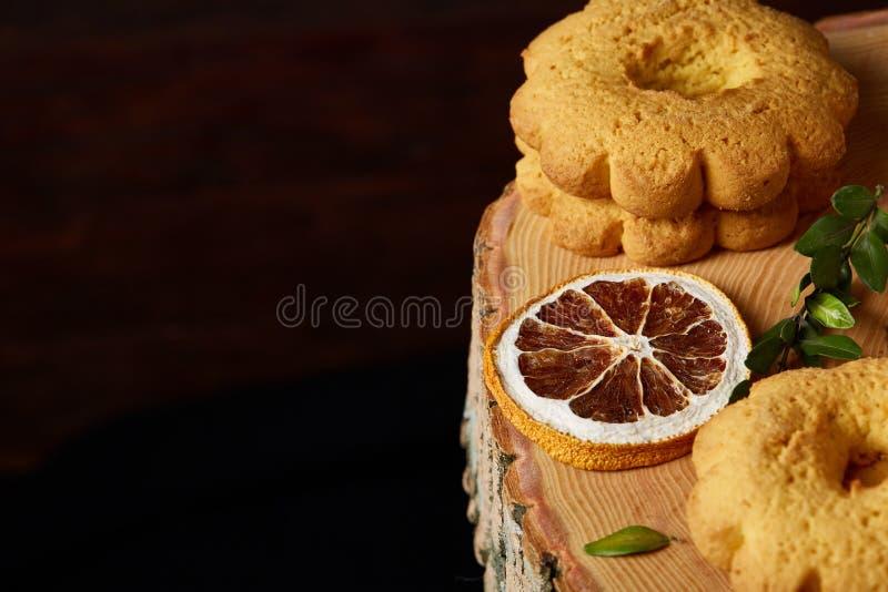 Concetto di Natale con l'assortimento dei biscotti e delle decorazioni su un ceppo sopra fondo di legno, fuoco selettivo fotografia stock