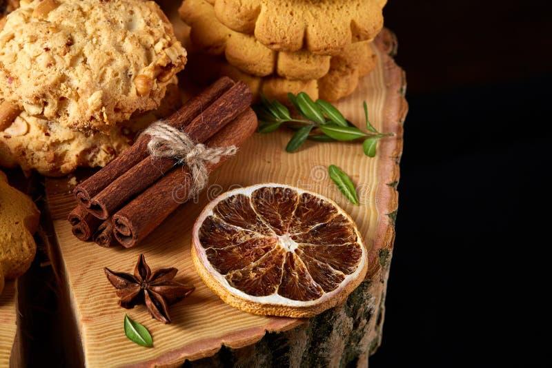Concetto di Natale con l'assortimento dei biscotti e delle decorazioni su un ceppo sopra fondo di legno, fuoco selettivo fotografia stock libera da diritti