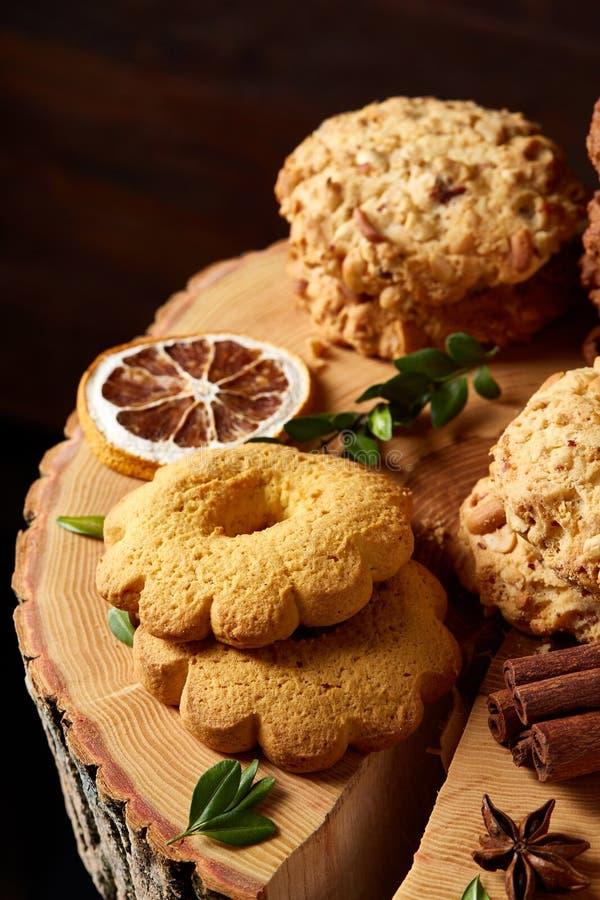 Concetto di Natale con l'assortimento dei biscotti e delle decorazioni su un ceppo sopra fondo di legno, fuoco selettivo immagini stock