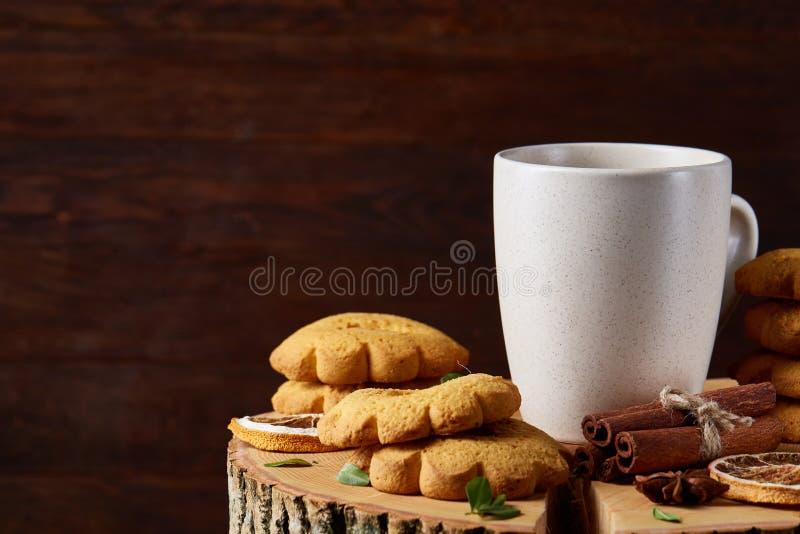 Concetto di Natale con una tazza bianca di tè, dei biscotti e delle decorazioni caldi su un ceppo sopra fondo di legno, fuoco sel immagini stock