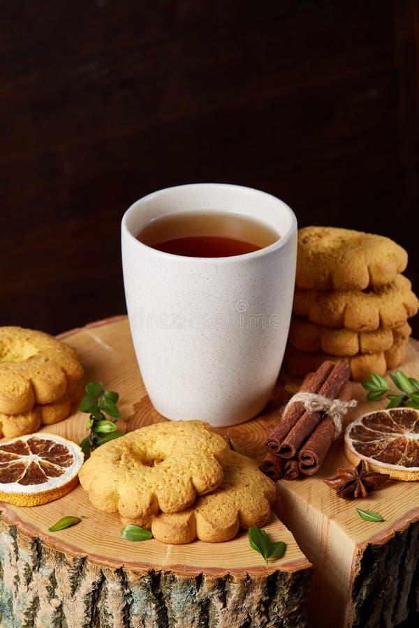 Concetto di Natale con una tazza bianca di tè, dei biscotti e delle decorazioni caldi su un ceppo sopra fondo di legno, fuoco sel immagine stock