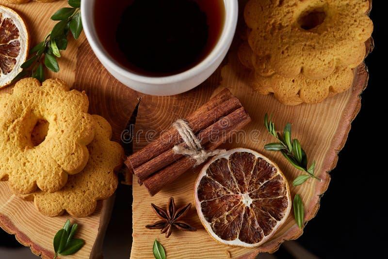 Concetto di Natale con una tazza bianca di tè, dei biscotti e delle decorazioni caldi su un ceppo sopra fondo di legno, fuoco sel fotografia stock
