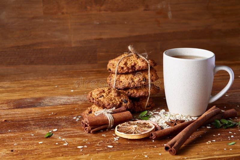 Concetto di Natale con una tazza di tè, dei biscotti e delle decorazioni caldi su un ceppo sopra fondo di legno, fuoco selettivo fotografia stock
