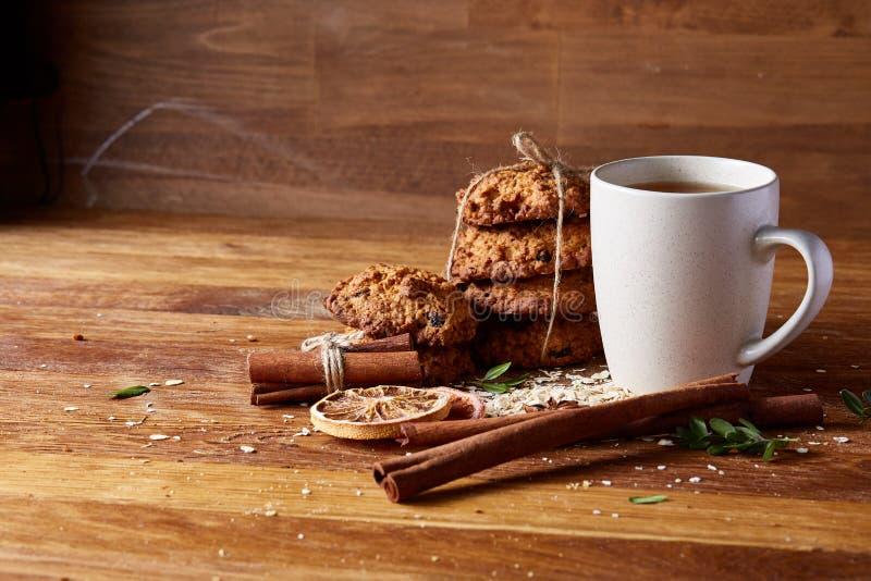 Concetto di Natale con una tazza di tè, dei biscotti e delle decorazioni caldi su un ceppo sopra fondo di legno, fuoco selettivo fotografie stock libere da diritti