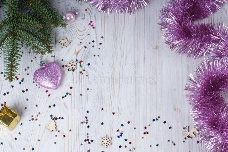 Concetto di Natale - decorazione del lamé di natale e cuore rosa sui rami di albero sempreverdi con lo spazio della copia immagine stock