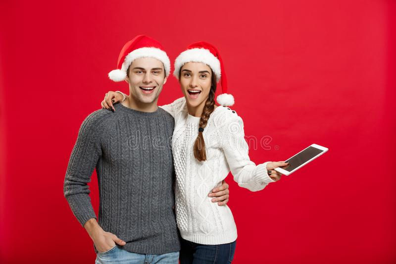 Concetto di Natale - giovane coppia felice in maglioni di natale che tengono compressa digitale fotografie stock libere da diritti