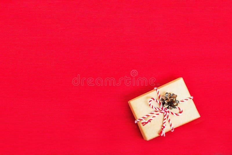 Concetto di Natale - un piccolo regalo in carta del mestiere su un fondo rosso del tessuto fotografia stock libera da diritti