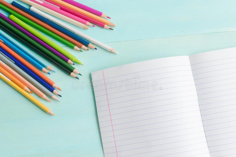Concetto di nuovo alla scuola Accessori della scuola, matite colorate, penna con il taccuino vuoto su fondo di legno blu immagini stock