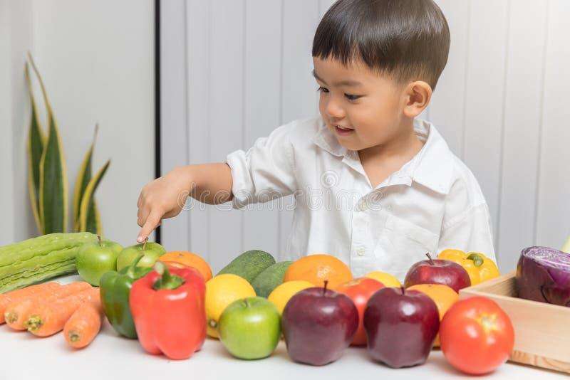 Concetto di nutrizione e sano Bambino che impara circa la nutrizione come scegliere cibo frutta e delle verdure fresche fotografia stock libera da diritti