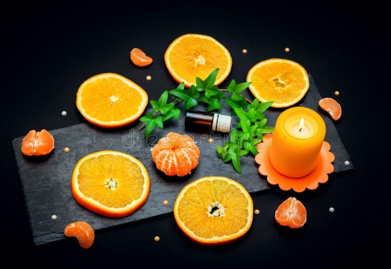 Concetto di olio di Citrus aroma - bottiglia di vetro con essenza, tangerina e fette arancioni immagini stock libere da diritti