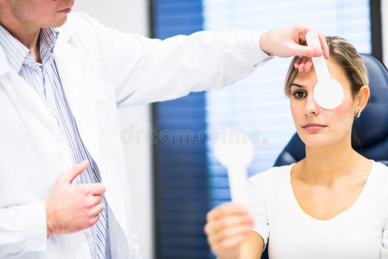 Concetto di optometria - giovane donna graziosa che fa i suoi esaminare occhi fotografia stock