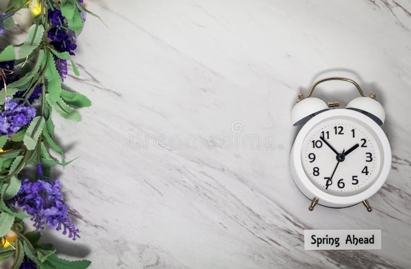 Concetto di ora legale della primavera avanti su marmo grigio con l'orologio bianco fotografia stock