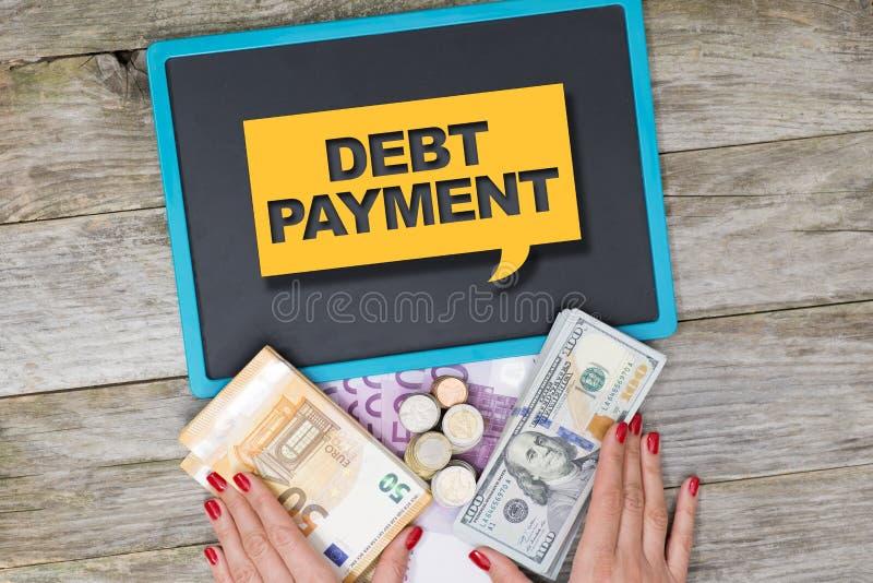 Concetto di pagamento di debito scritto sul segno giallo sulla lavagna con denaro contante per i risarcimenti di prestiti fotografia stock libera da diritti