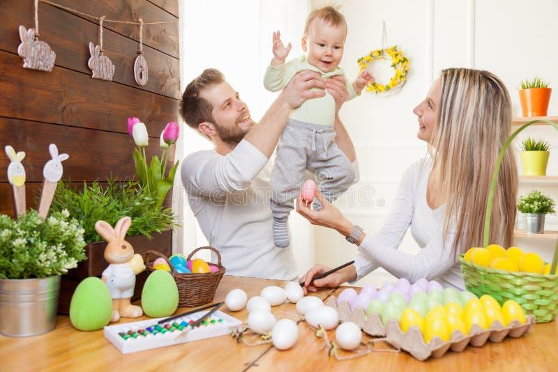 Concetto di Pasqua Madre felice e padre che preparano decorazione domestica con il loro bambino per le vacanze di Pasqua fotografie stock