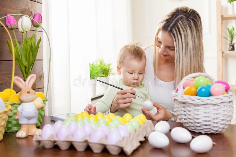 Concetto di Pasqua Madre felice e suo il bambino sveglio che si preparano per Pasqua immagini stock