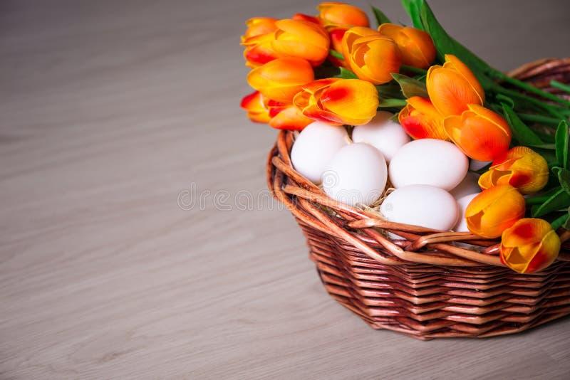Concetto di Pasqua - uova bianche e merce nel carrello dei tulipani sulla tavola di legno fotografia stock libera da diritti