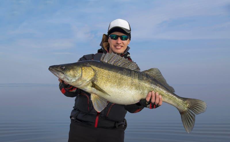 Concetto di pesca Pescatore felice con il grande trofeo del pesce della sabbiatrice dello zander fotografia stock libera da diritti