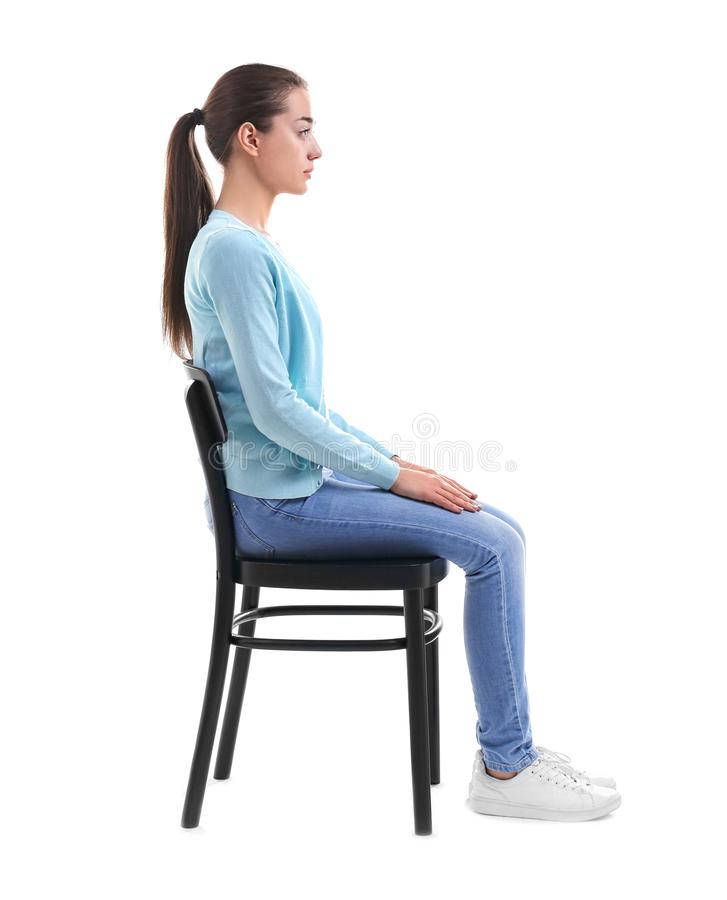 Concetto di posizione Giovane donna che si siede sulla presidenza fotografia stock