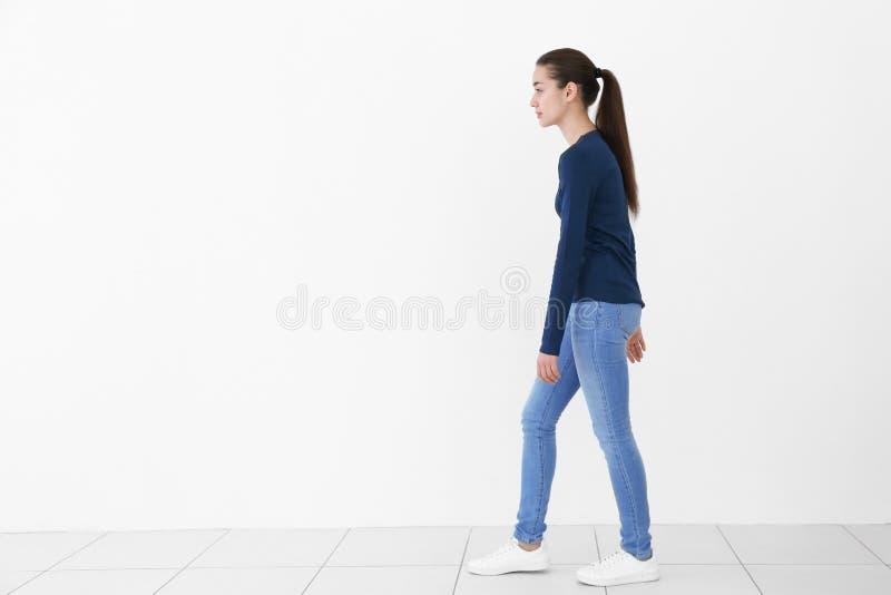Concetto di posizione Giovane donna su priorità bassa bianca fotografie stock
