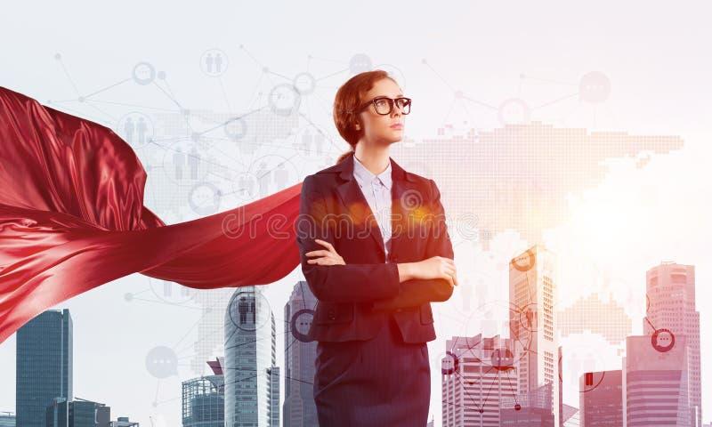 Concetto di potere e di successo con il supereroe della donna di affari in grande città fotografia stock
