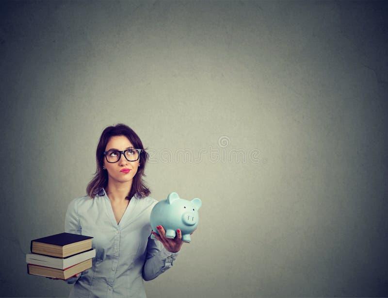 Concetto di prestito dello studente Donna con il mucchio dei libri e del porcellino salvadanaio in pieno del debito che ripensa p fotografie stock