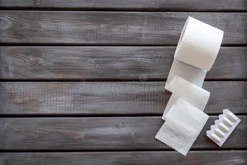Concetto di proctologia con il rotolo della carta igienica e la supposta rettale sul modello di legno di vista superiore del fond fotografia stock libera da diritti