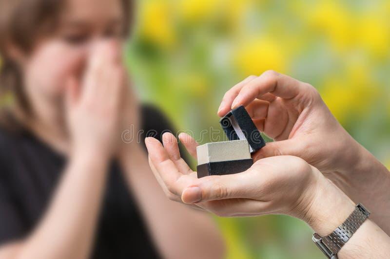 Concetto di proposta di nozze L'uomo tiene la scatola con la fede nuziale in mani fotografie stock libere da diritti