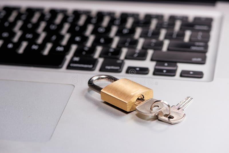 Concetto di protezione dei dati e di sicurezza informatica Computer portatile con una serratura bloccata e chiave su  fotografia stock