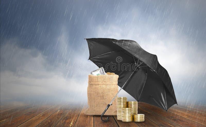 Concetto di protezione, ombrello nero proteggere pila di monete e di borsa del sacco con le banconote in dollari su fondo di legn fotografie stock libere da diritti