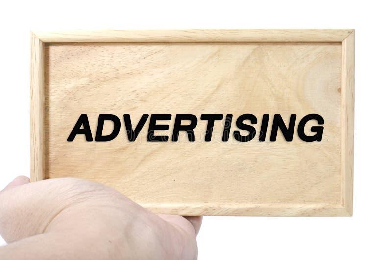 Concetto di pubblicità e di affari mano che tiene legno normale con la pubblicità di parola fotografie stock libere da diritti