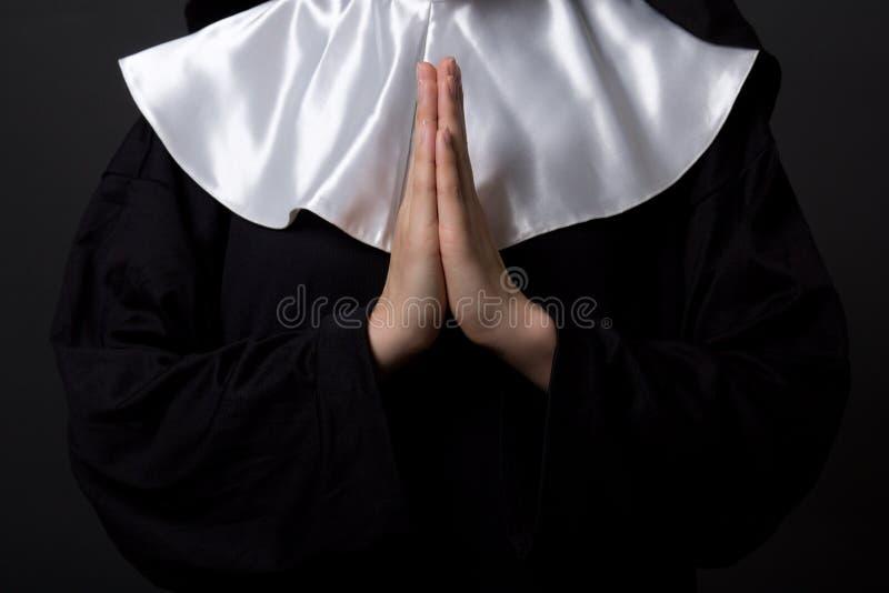 Concetto di religione - mani della suora della donna che pregano su grey fotografia stock libera da diritti