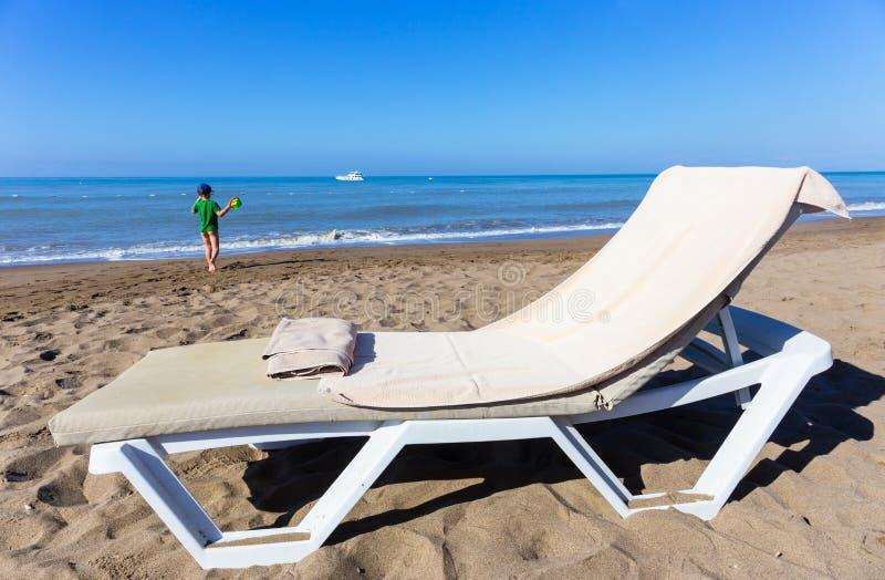 Concetto di resto dalla chaise-lounge marina con l'asciugamano ed il bambino di spiaggia che camminano al mare immagini stock libere da diritti