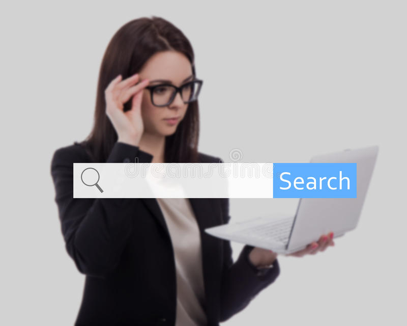 Concetto di ricerca di Internet - giovane donna di affari che per mezzo del computer portatile e fotografia stock libera da diritti