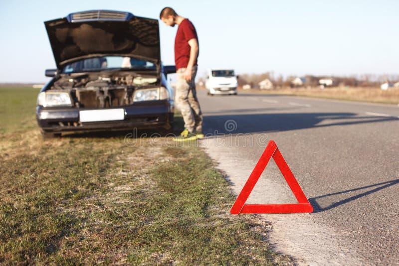Concetto di ripartizione dell'automobile Il driver impotente dell'uomo sta vicino brocken l'auto con il cappuccio aperto, ha prob immagini stock libere da diritti