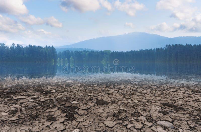 Concetto di riscaldamento globale e del mutamento climatico Lago asciutto e terra di siccità con la foresta e cielo blu con il pa immagini stock libere da diritti