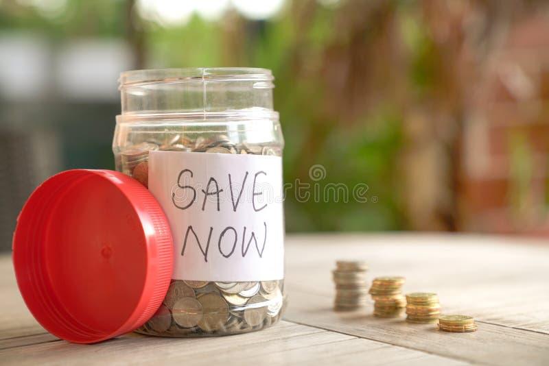 Concetto di risparmio dei soldi: monete in contenitore ed impilate sulla tavola immagine stock