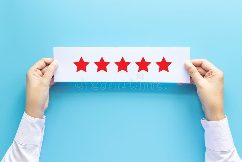 Concetto di risposte e di valutazione il cliente che tiene la carta con l'esame soddisfatto vicino dà la stella cinque per esperi immagini stock