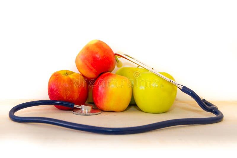 Concetto di salute con le mele e lo stetoscopio verdi e rossi immagine stock