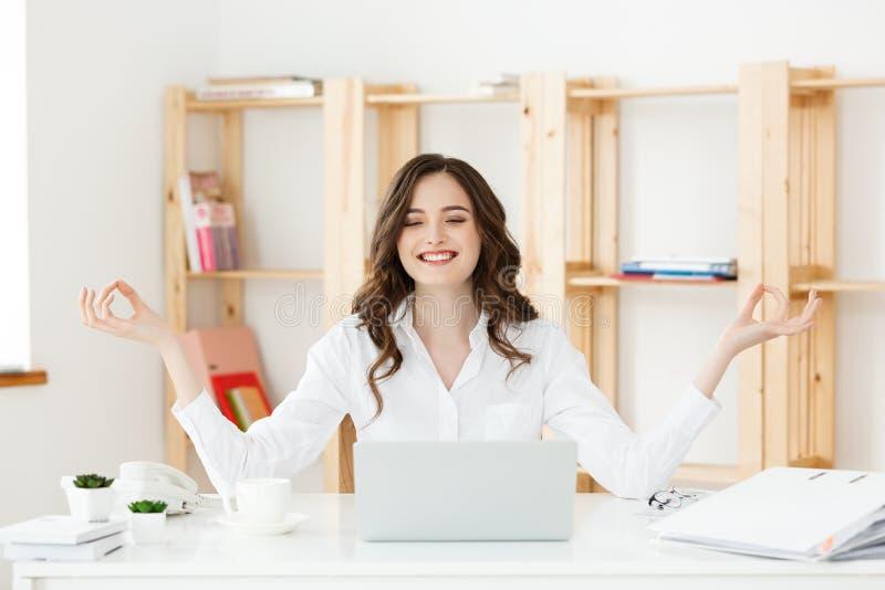 Concetto di salute e di affari: Giovane donna vicino al computer portatile, meditazione di pratica del ritratto alla scrivania, d fotografia stock libera da diritti