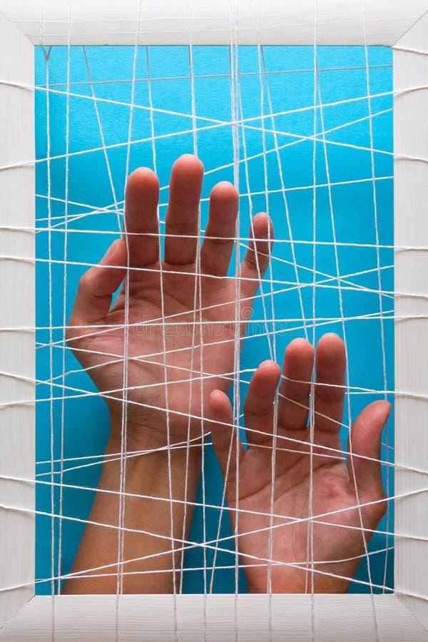 Concetto di salute mentale Le mani del ` s delle donne provano a rompere i fetters su fondo blu immagini stock libere da diritti