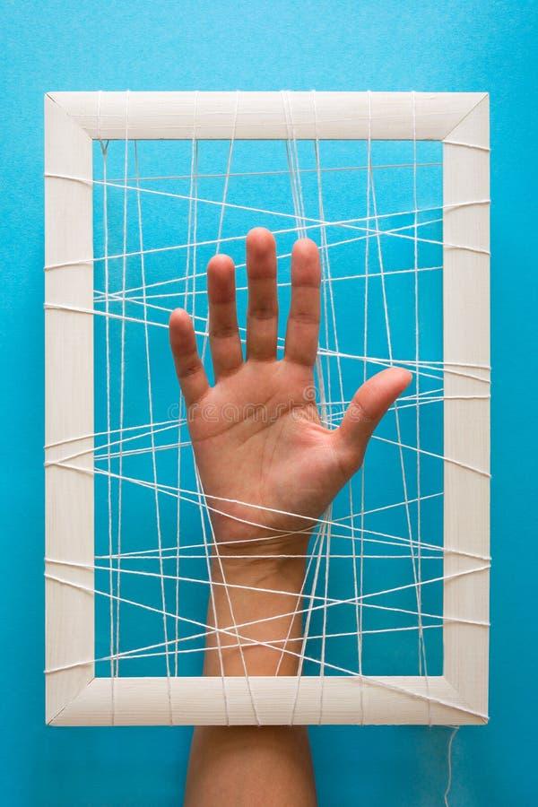Concetto di salute mentale Le mani del ` s delle donne provano a rompere i fetters su fondo blu fotografia stock libera da diritti