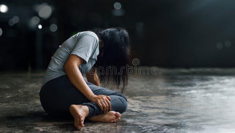 Concetto di salute mentale di PTSD Disordine post - traumatico di sforzo La donna depressa che si siede da solo sul pavimento nel immagini stock