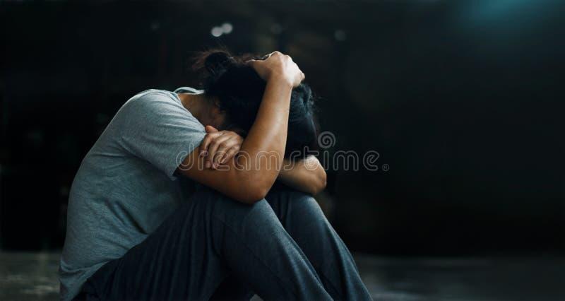Concetto di salute mentale di PTSD Disordine post - traumatico di sforzo La donna depressa che si siede da solo sul pavimento nel immagini stock libere da diritti