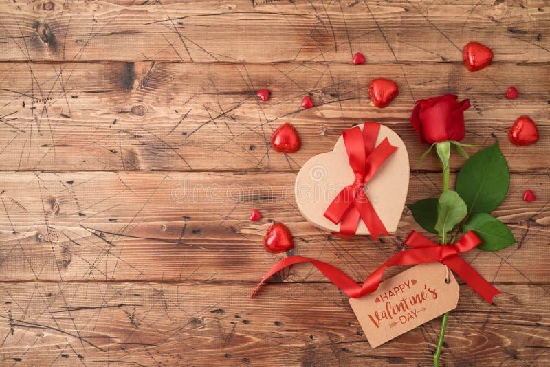 Concetto di San Valentino con il fiore, il contenitore di regalo ed il cioccolato rosa di forma del cuore su fondo di legno fotografia stock libera da diritti