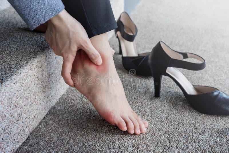 Concetto di sanità Sofferenza femminile dal dolore in caviglia o nel piede fotografia stock