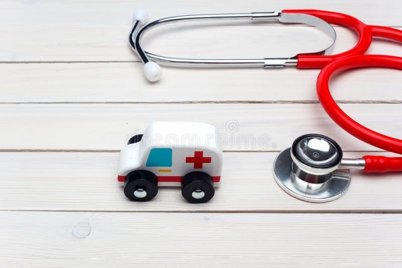 Concetto di servizio di ambulanza Giocattolo dell'ambulanza vicino allo stetoscopio su fondo di legno bianco immagini stock libere da diritti