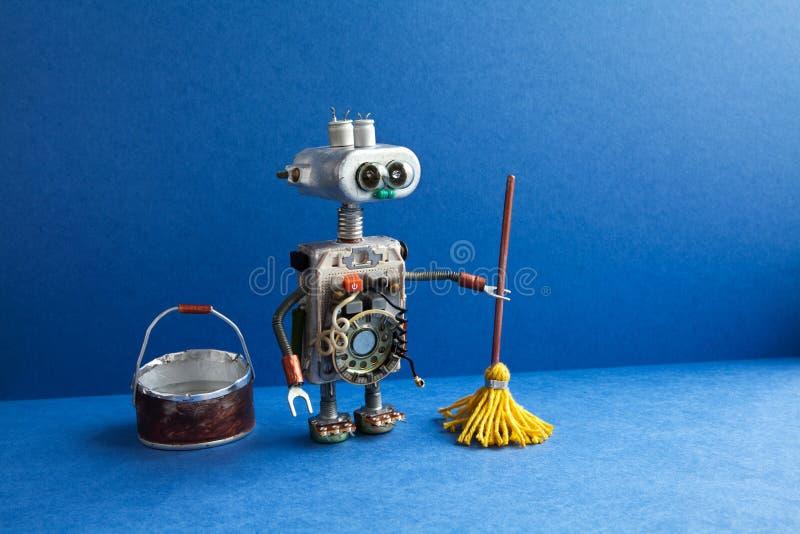 Concetto di servizio in camera di lavaggio di pulizia Pulitore del robot con la zazzera gialla, secchio di acqua, pavimento ampio immagini stock