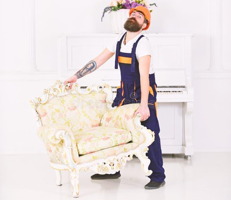 Concetto di servizio di distribuzione Il corriere consegna la mobilia nel caso di va via, la rilocazione Uomo con la barba, lavor immagine stock