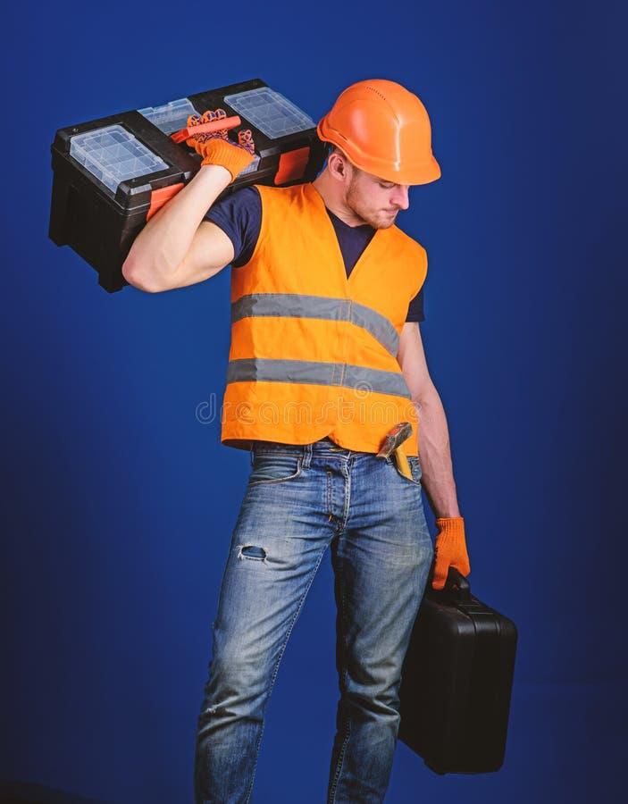 Concetto di servizio di riparazione L'uomo in casco, casco tiene la cassetta portautensili e la valigia con gli strumenti, fondo  fotografie stock