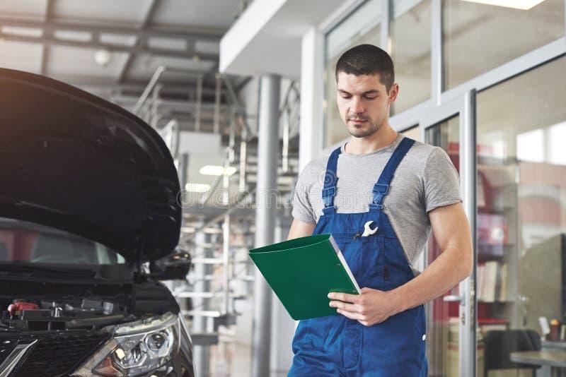 Concetto di servizio, di riparazione, di manutenzione e della gente dell'automobile - uomo o fabbro del meccanico con la lavagna  immagine stock libera da diritti